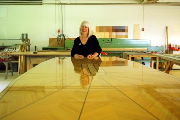 Susan Saarinen säteilee nähtyään kuinka hänen isoisänsä Eliel Saarisen muotoiluperinne elää Vehmersalmen Tetrimäessä. Kuvan pöytä toimitettiin Teksasiin.